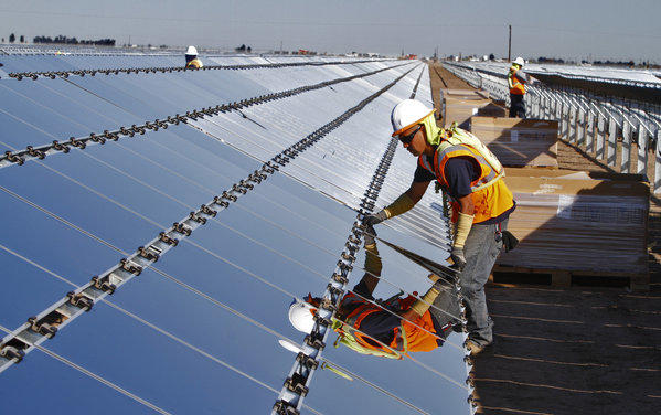 In 2011, U.S. firms held a $1.63 billion trade surplus with China in clean energy goods. Above, a worker installs a photovoltaic panel at the Tenaska Imperial Solar Energy South project in the Imperial Valley west of El Centro, Calif., last month.