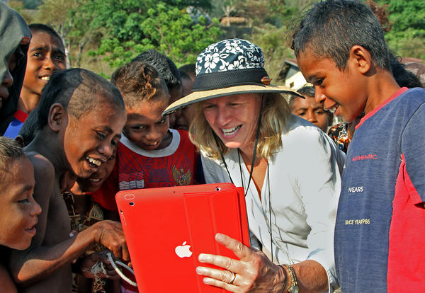 Author Nancy Baron shows village children a picture she took of them using her iPad.