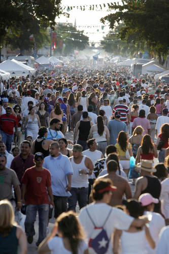 "Miami, UNITED STATES: A large crowd of people walk on 8th street during the ""Calle Ocho Festival"" 11 March 2007. Hundreds of thousands of people partcipated in the 23 block long street party billed as the nation's largest street festival. AFP PHOTO/  Roberto SCHMIDT (Photo credit should read ROBERTO SCHMIDT/AFP/Getty Images)"
