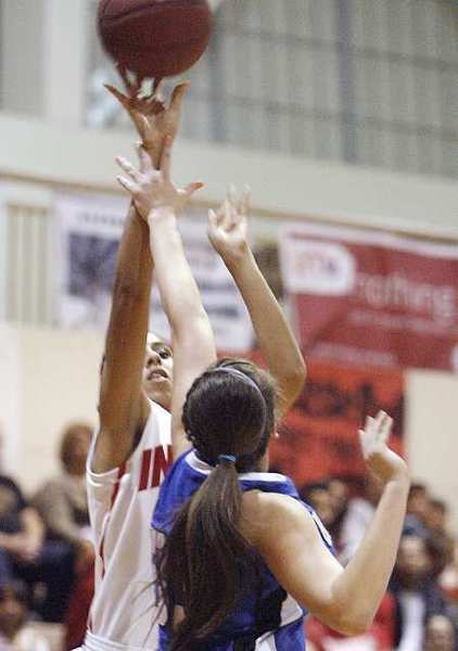 Burroughs' Aysia Shellmire goes up for a shot past Burbank defender Courtney Seidler on Friday, January 28, 2013.