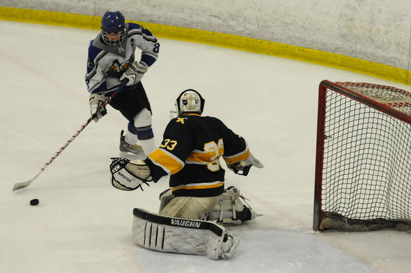 East Catholic's Dan Lemieux (8) takes a shot against Trinity Catholic's goalie Kyle Odiemo, 33, in the third period. East Catholic beat Trinity Catholic 5-2 in the first round of the Division II CIAC high school hockey tournament at the Champions Skating Center in Cromwell Tuesday night.