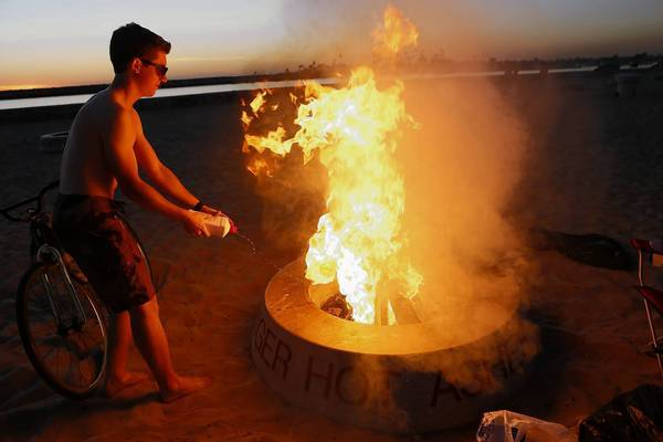 James Hughes adds fuel to the blaze in a fire ring at Corona Del Mar State Beach.