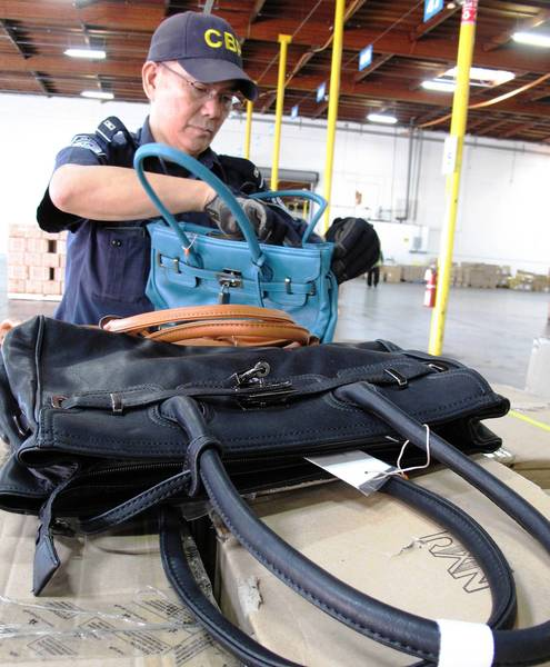 Customs officer Jesus Uyquiengco examines some of the 1,500 counterfeit Hermes handbags that were seized at the Port of Los Angeles.