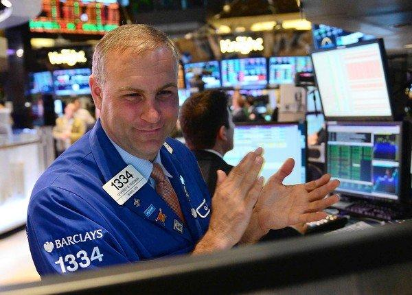Traders react at the end of trading Tuesday at the New York Stock Exchange. The Dow Jones industrial average closed at 14,253.77, a new all-time high. Broader stock indexes have also been hovering near all-time records.