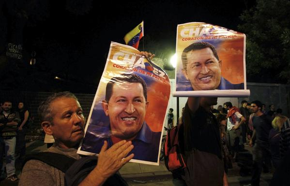 Supporters of Venezuela's President Hugo Chavez show pictures of him as they react to the announcement of his death outside the Venezuelan Embassy in Buenos Aires, Argentina. Chavez died on Tuesday after a two-year battle with cancer, ending 14 years of divisive rule.