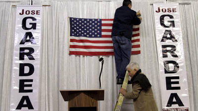 Campaign supporter Eric Ortiz hangs the flag as Guadalupe Davalos steadies the ladder at Jose Gardea's campaign party space in Los Angeles.