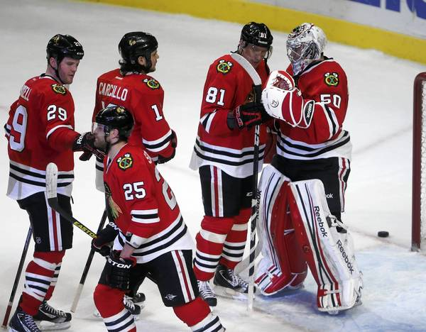 Marian Hossa (81) and goalie Corey Crawford (50) celebrate over the Wild.