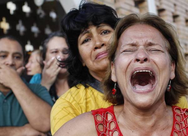 Supporters of Venezuela's President Hugo Chavez react to the announcement of his death outside his hospital in Caracas, March 5, 2013. Chavez has died after a two-year battle with cancer, ending the socialist leader's 14-year rule of the South American country, Vice President Nicolas Maduro said in a televised speech on Tuesday.