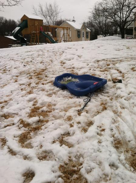 A sled stands abandoned in a yard on Baywood Lane in Jarrettsville Wednesday morning as snow transitioned to rain.