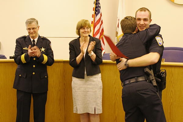 Evanston Officer Sean O'Brien, right, hugs a fellow officer he was credited with saving during a ceremony in 2010. O'Brien is now being commended for rescuing a boy from the Des Plaines River. In both cases, he was off-duty at the time.