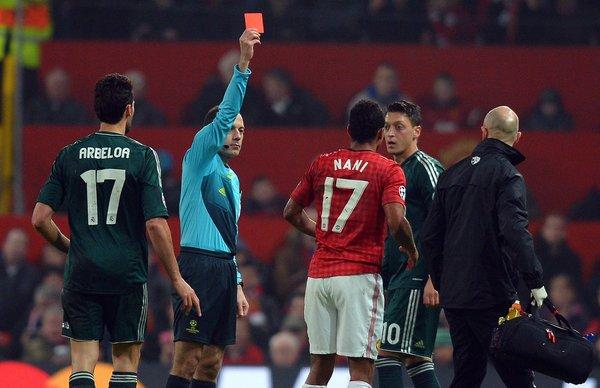Turkish referee Cuneyt Cakir shows Manchester United midfielder Nani the red card to send him off during a Champions League match against Real Madrid.