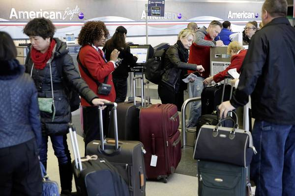 Travelers wait at American Airlines in Terminal 3 as operations return to normal at O'Hare International Airport.