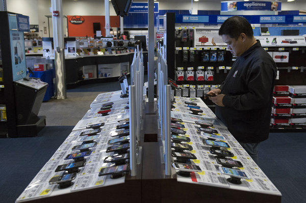 A shopper views mobile phones at a Best Buy store in San Francisco. Unlocking cellphones makes it possible for consumers to use their device with a carrier other than the one from which they purchased the phone.