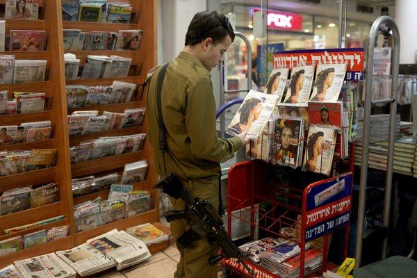 An Israeli soldier looks at a Playboy magazine in a kiosk in Jerusalem.