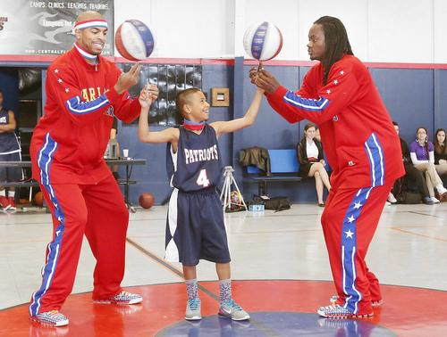 Harlem Globetrotters stars Hammer Harrison, left, and Slick Willie Shaw, right, help eleven-year-old Julian Newman spin two basketballs on his fingers during an appearance at the at the Downey Christian School in Orlando on Wednesday, March 6, 2013.  (Stephen M. Dowell/Orlando Sentinel)