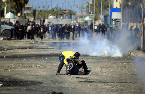 An Egyptian protester evacuates a wounded man during clashes with riot police near the state security building in Port Said, Egypt, on Wednesday.