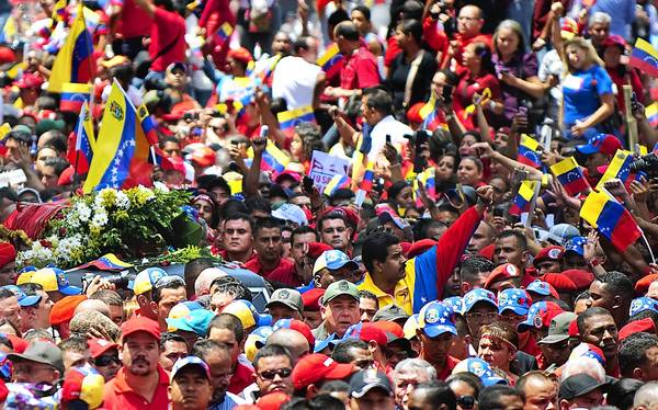 Venezuelan acting President Nicolas Maduro, center, raises his fist while accompanying the funeral cortege of the late Venezuelan President Hugo Chavez on its way to the Military Academy in Caracas.