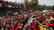 "CARACAS, Venezuela-- In a massive outpouring of grief for Venezuela's late <a href=""http://www.latimes.com/news/obituaries/la-me-hugo-chavez-20130306,0,3058426.story"">President Hugo Chavez</a>, hundreds of thousands of his red-shirted, fervent and often tearful followers lined a route through the capital where his coffin was being carried on its way to a military base where it will lie in state until his funeral on Friday."