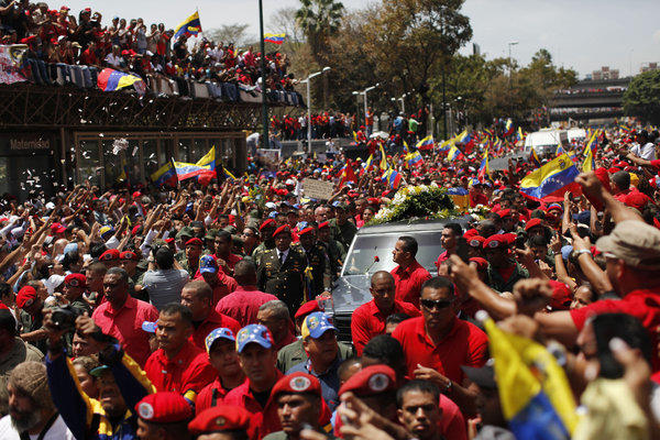 Supporters of Venezuela's late President Hugo Chavez crowd the street to watch his coffin pass by.