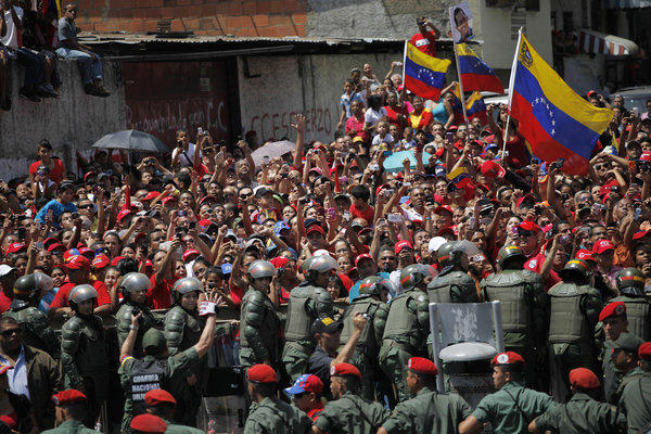 Supporters of late Venezuelan President Hugo Chavez crowd a street in Caracas to watch his coffin pass by as it is taken from the hospital where he died Tuesday. The coffin will be placed at a military academy where it will remain until his funeral.