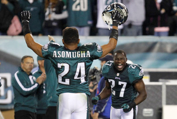 Philadelphia Eagles defenders Nnamdi Asomugha (24) and Brandon Hughes (27) celebrate a win over the New York Giants after the fourth quarter of their NFL football game in Philadelphia, Pennsylvania, September 30, 2012.
