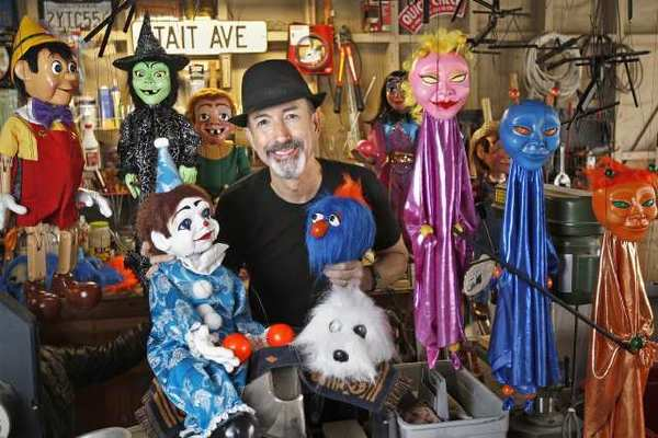 Puppeteer Tait Hill at his home in Huntington Beach on Tuesday. For more than 20 years, Hill has been performing marionette puppet shows, and later this month will bring his Pullin' Strings Puppet Productions to the Orange County Marketplace.