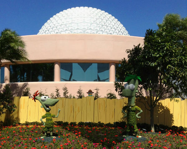 "Phineas and Ferb, characters from the Disney Channel animated series ""Phineas & Ferb,"" are positioned in the garden behind Spaceship Earth. (Agent P look on, see?)"