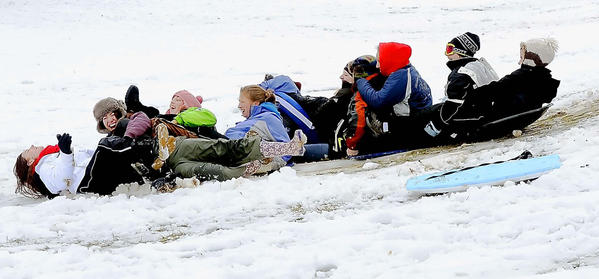 Students at Wilson College in Chambersburg, Pa., use saucers, their bottoms and food trays Wednesday afternoon to slide down a hill behind Lortz Hall.