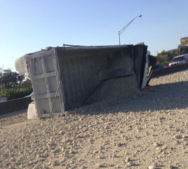 A dump truck rolled over on the northbound Florida Turnpike in Davie tying up traffic for miles