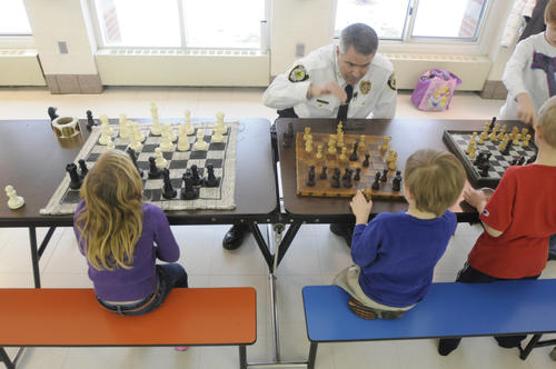 Chief Arciero prepares to make his move against first grader Jackson Senecal, 6, as two other first graders, Bethany Douglas, 6, left, and Ian Clark, 6, right, wait for the chief to come back for his next move. Arciero was playing three games at once.