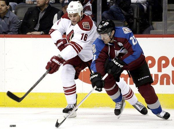 Coyotes defenseman Rusty Klesla fights for possession of the puck against Avalanche right wing Milan Hejduk during the second period of a game last month.