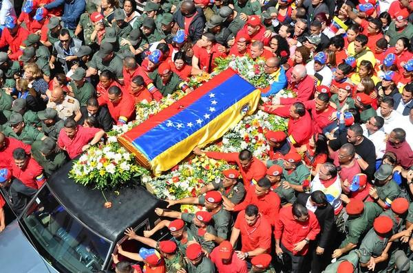 President Hugo Chavez's coffin is thronged as it is carried through Caracas to the Venezuelan Military Academy, where his body will lie in state until a funeral Friday.