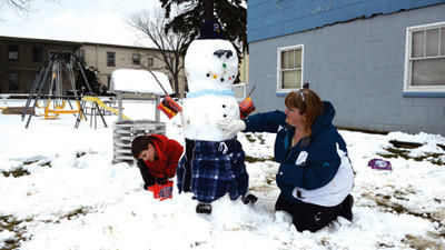 "Brady Brewer, 7, and his mother, Pam, spent Wednesday outside shoveling and building this summer-themed snowman near their home along West Garrett Street in Somerset. Decked out in swimming trunks, sunglasses, sandals and a Hawaiian lei, the two said that their frozen friend is an encouragement to ""think spring."""