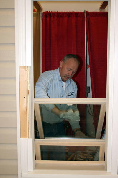 Paul Zeger, owner of A-Light Windows and Doors of Chambersburg, Pa., wipes down a window Wednesday while preparing his display for the 30th annual Franklin County Builders Show this weekend in Waynesboro, Pa.