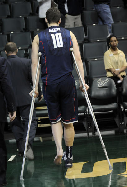 Tyler Olander is checked by the UConn trainer as he leaves the floor on crutches at the end of the game in Tampa. The UConn team is suffering injuries to many of their starters. The UConn men met the University of South Florida in Tampa for their second to last game of the season Wednesday night. UConn lost, 65-51.