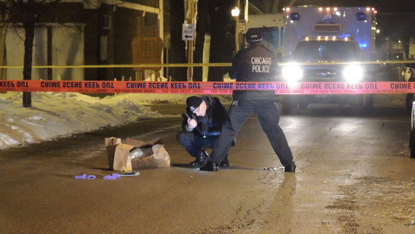 Police look at evidence in the 1300 block of North St. Louis Avenue in the Humboldt Park neighborhood.