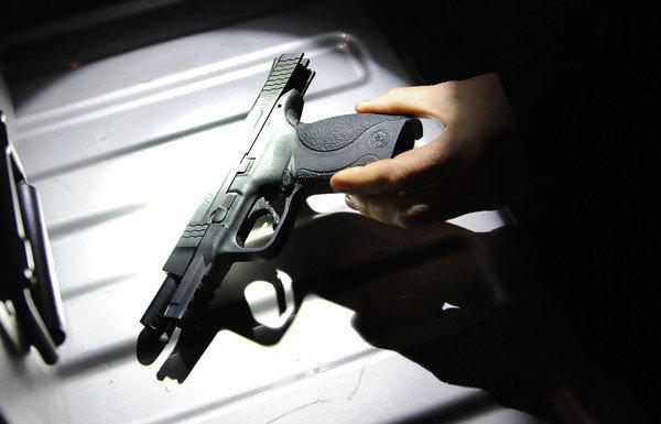 A Department of Justice law enforcement officer holds a handgun seized from a man who was not legally allowed to own the gun.