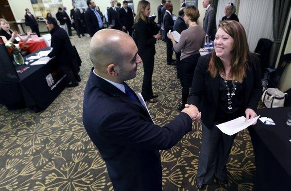Sayed Mouawad of Providence, R.I., shakes hands with Jillian Wallace of Matix Inc. during a job fair in Boston.