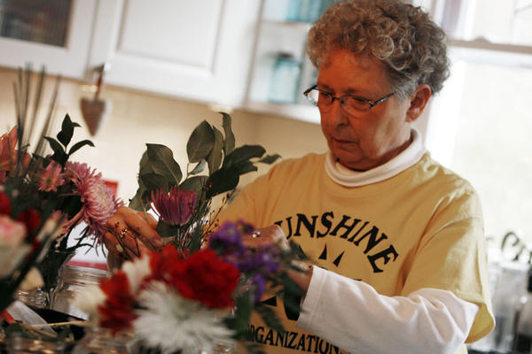 Priscilla Shideler uses the assortment of flowers on the kitchen island to fill a vase.