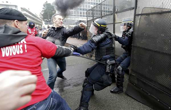 Protestors fight with French CRS riot police in front of Goodyear Dunlop France headquarters during a demonstration against job cuts in Rueil Malmaison, near Paris March 7, 2013. Goodyear confirmed in January the project to close a French plant near the northern city of Amiens, which, if undertaken, would lead to the layoff of 1,173 jobs.