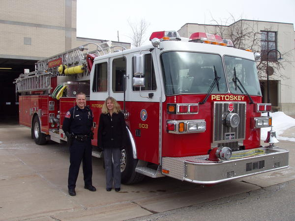 Petoskey Department of Public Safety Lieutenant Adrian Karr (left) shows a Petoskey firetruck to Gail Kloss, finance director of the Women's Resource Center of Northern Michigan. A ride for three people on the firetruck is one of the unique items up for bid during the Women's Resource Center FUNdraiser set Wednesday, March 13.