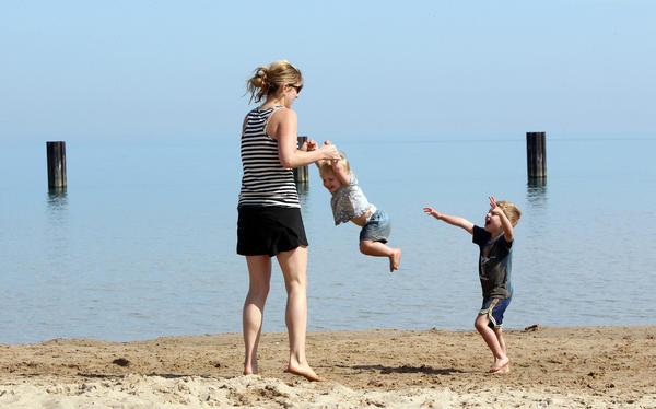 Jennie Frampton plays with daughter Lola, 2, and son Curtis, 4, on the lakefront during unseasonably warm weather on March 22, 2012.