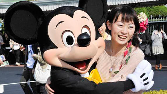 Mickey Mouse poses with a visitor at Tokyo Disneyland after the theme park reopened following the devastating Japanese earthquake in March.