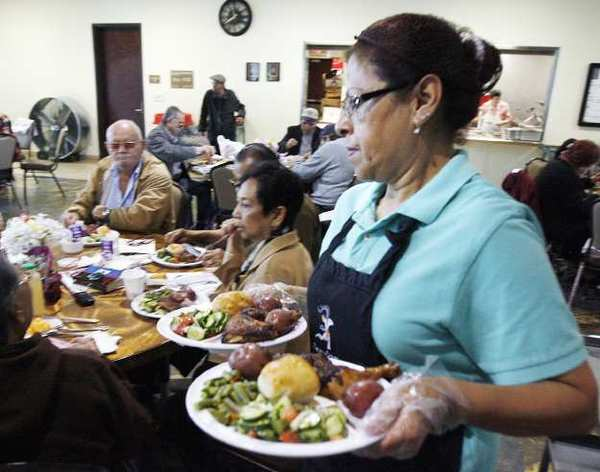 Food server Susanna Leos serves dinners to guests who have a ticket at the Adult Recreation Center in Glendale.