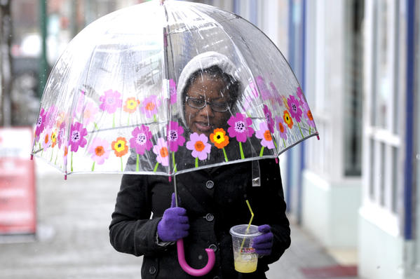Tanya Green, 22, of Hartford broke out a colorful umbrella on a wet day along Park Street in Hartford where she was en route to her doctor. Green was sipping orange juice along the way.