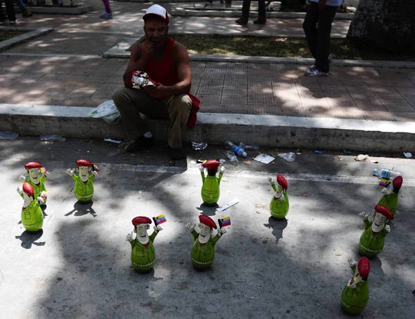 A street vendor offers dolls of Venezuela's late President Hugo Chavez in Caracas.