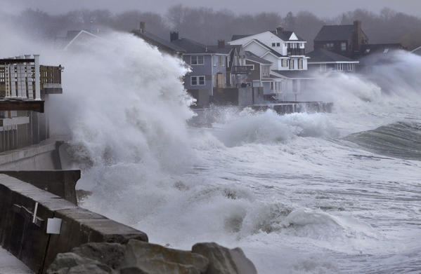 Ocean waves crash over a seawall and into houses along the coast in Scituate, Mass., Thursday, ahead of a winter storm that was bringing strong winds to coastal areas.