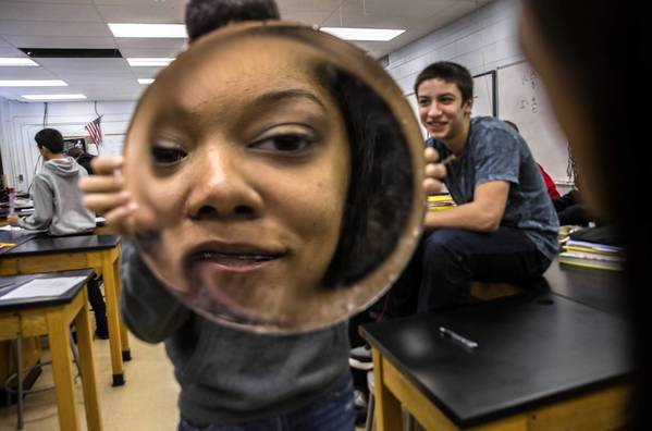 Ninth-grade physics students, Andrea McKinley, 15 (reflected), Logan Kirnbauer, 15, holding, and Andrew Arredondo, 15, learn optics in class at Tinley Park High School.