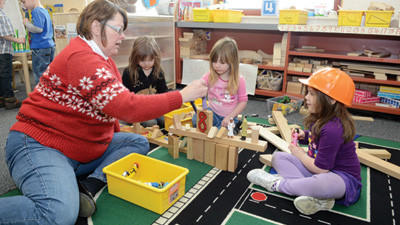 Lead teacher Ronda Beckner works in the block area with Emily Coddington, 4, April Shaulis, 3 and Desiree DuVull, 5. The block area uses building, stacking, sorting and measuring to learn sizes and shapes and how to work together.