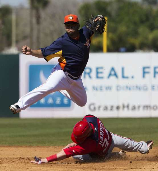 Houston Astros second baseman Jose Altuve leaps over the Washington Nationals outfield Bryce Harper while turning a double play during the fourth inning of their spring training baseball game in Kissimmee, Florida March 7, 2013.